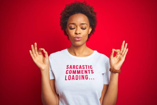 mujer afroamericana con comentarios sarcásticos camiseta sobre fondo rojo aislado relajarse y sonreír con los ojos cerrados haciendo gesto de meditación con los dedos. concepto de yoga. - ironía fotografías e imágenes de stock