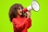 istock African american woman wearing sunglasses communicates shouting loud holding a megaphone, expressing success and positive concept, idea for marketing or sales 1043969292