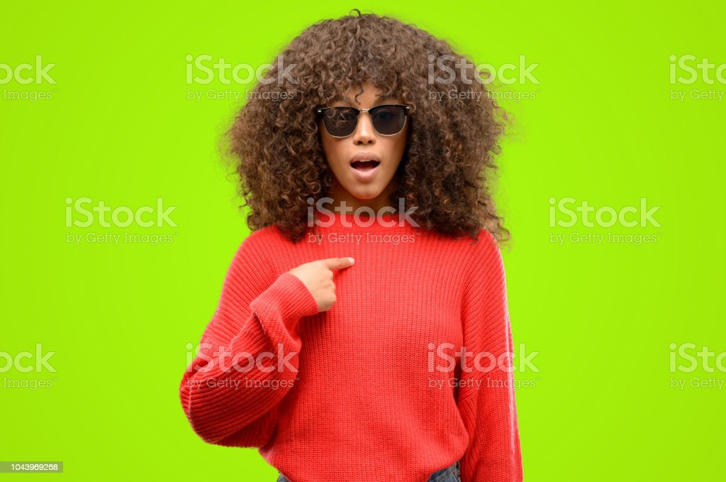 African american woman wearing sunglasses happy and surprised...