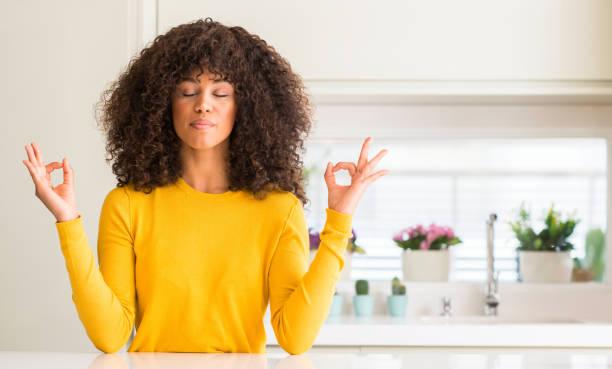 afrikanische amerikanische frau, die mit gelben pullover in küche entspannen und lächelnd mit augen geschlossen meditation geste mit den fingern zu tun. yoga-konzept. - geschlossene küchen stock-fotos und bilder