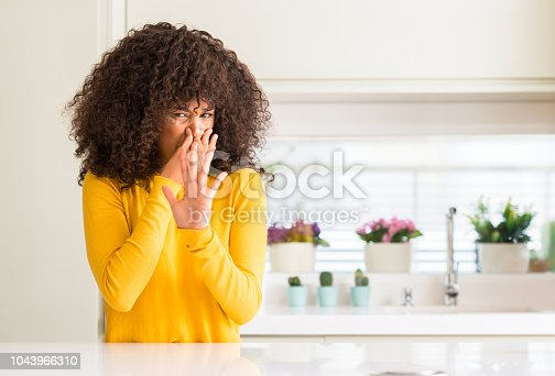 African american woman wearing yellow sweater at kitchen smelling something stinky and disgusting, intolerable smell, holding breath with fingers on nose. Bad smells concept.