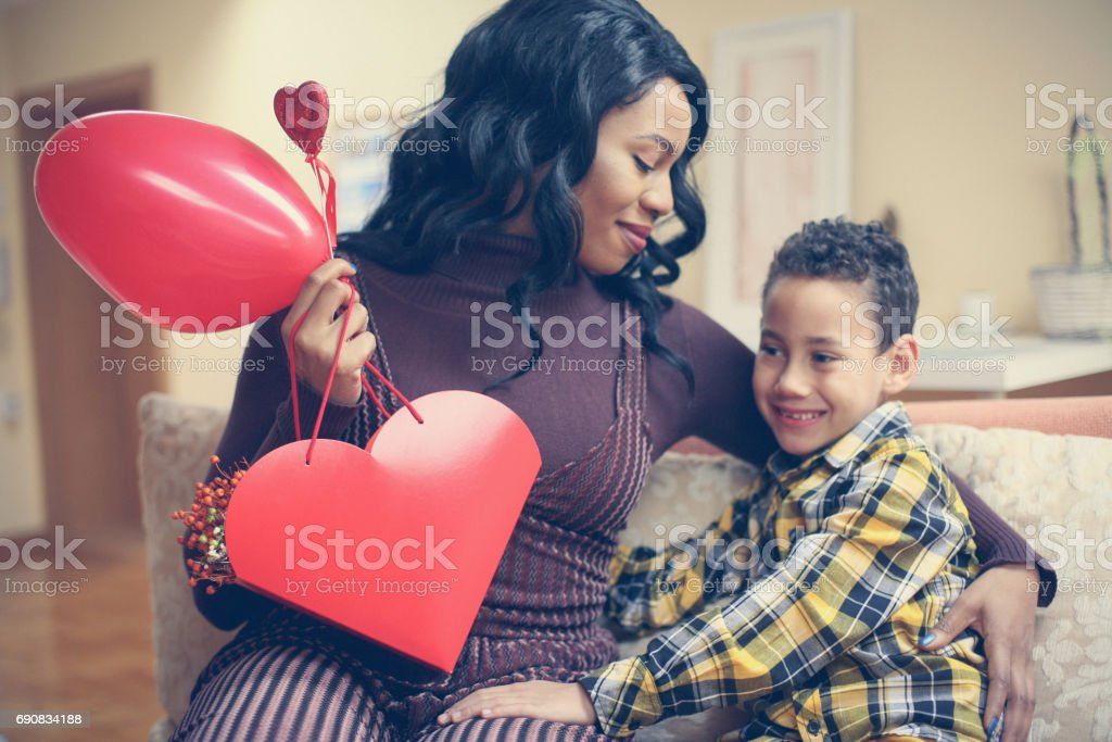 African American woman wit her son. African American boy giving a...
