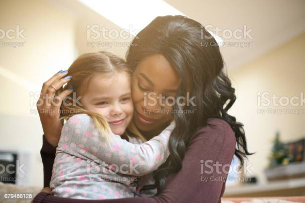 "African American woman playing with girl. Woman hugging her adopted daughter.""n"