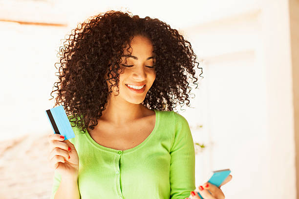 African american woman with credit card and mobile phone stock photo