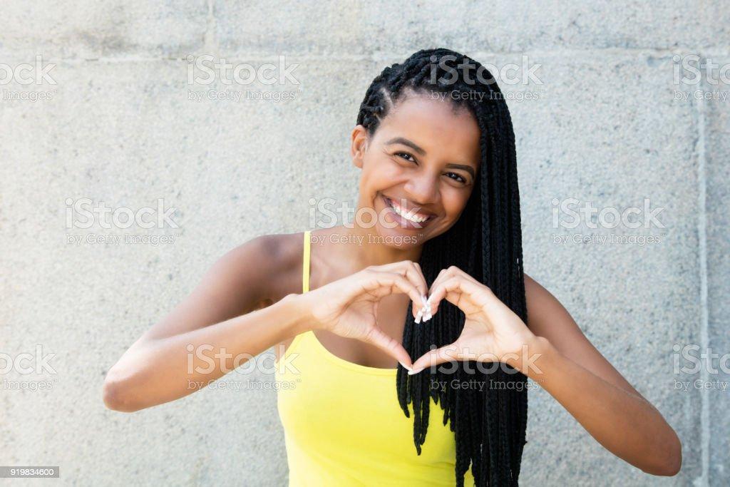 Mulher afro-americana com dreadlocks no amor mostra o coração com as mãos - foto de acervo