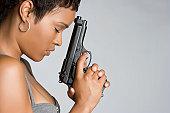 Sad african american woman holding gun