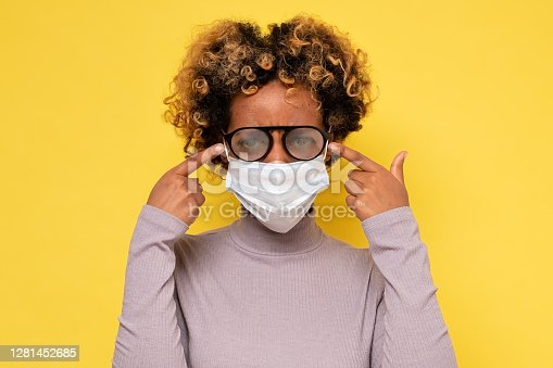 Cute african american woman with foggy glasses caused by wearing a COVID protective mask
