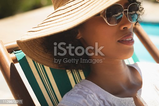Close-up of beautiful young African American woman with hat and sunglasses relaxing on sun lounger in her backyard on a sunny day. She seems to be on vacation