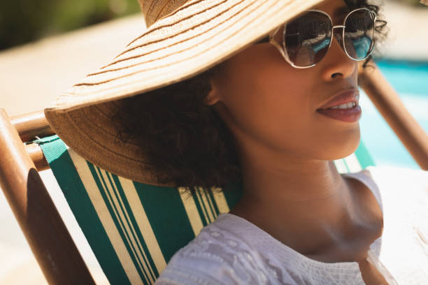 African American woman with hat and sunglasses relaxing on sun lounger in her backyard stock photo