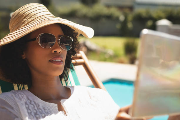 African American woman with hat and sunglasses using digital tablet in her backyard stock photo