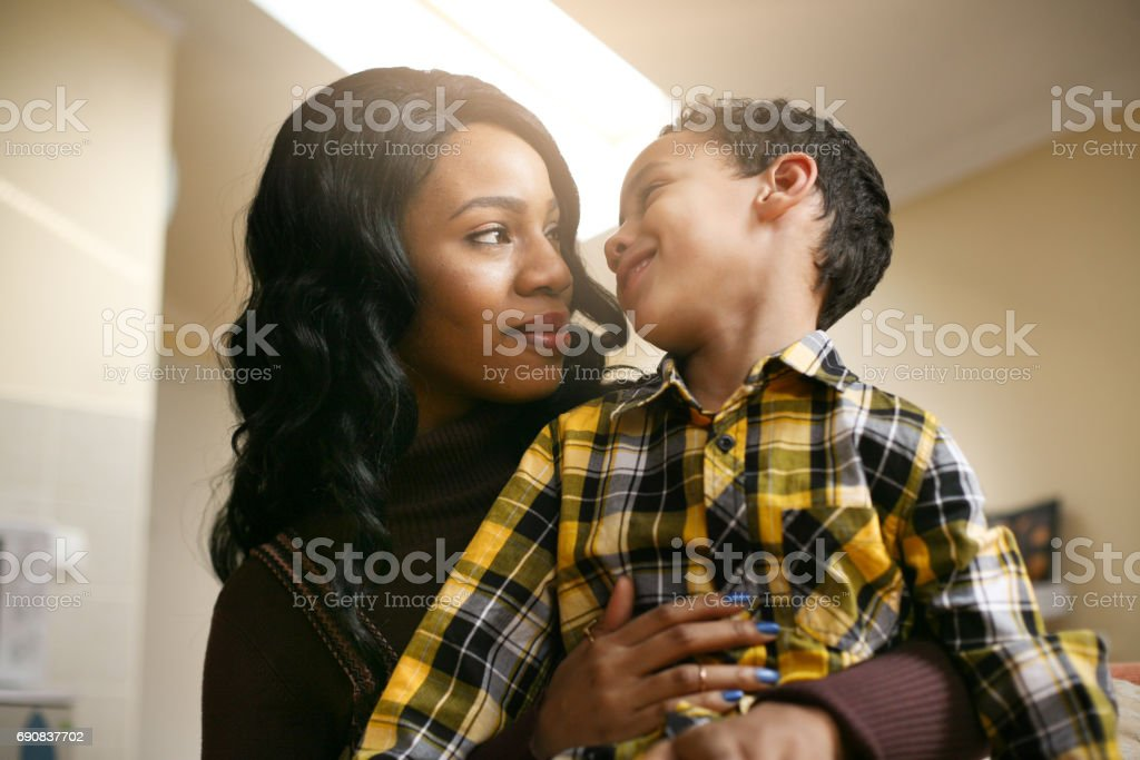African American woman with her son. African American woman spending time with her son at home. Looking each other. stock photo
