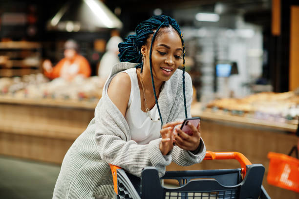 African american woman with shopping cart trolley in the supermarket store. stock photo