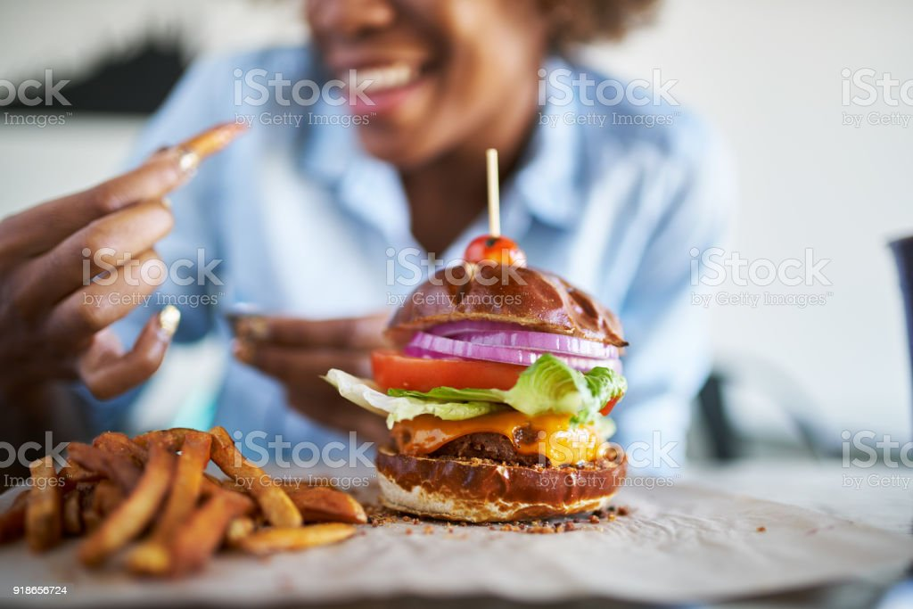 african american woman with vegan meatless burger meal with selective...