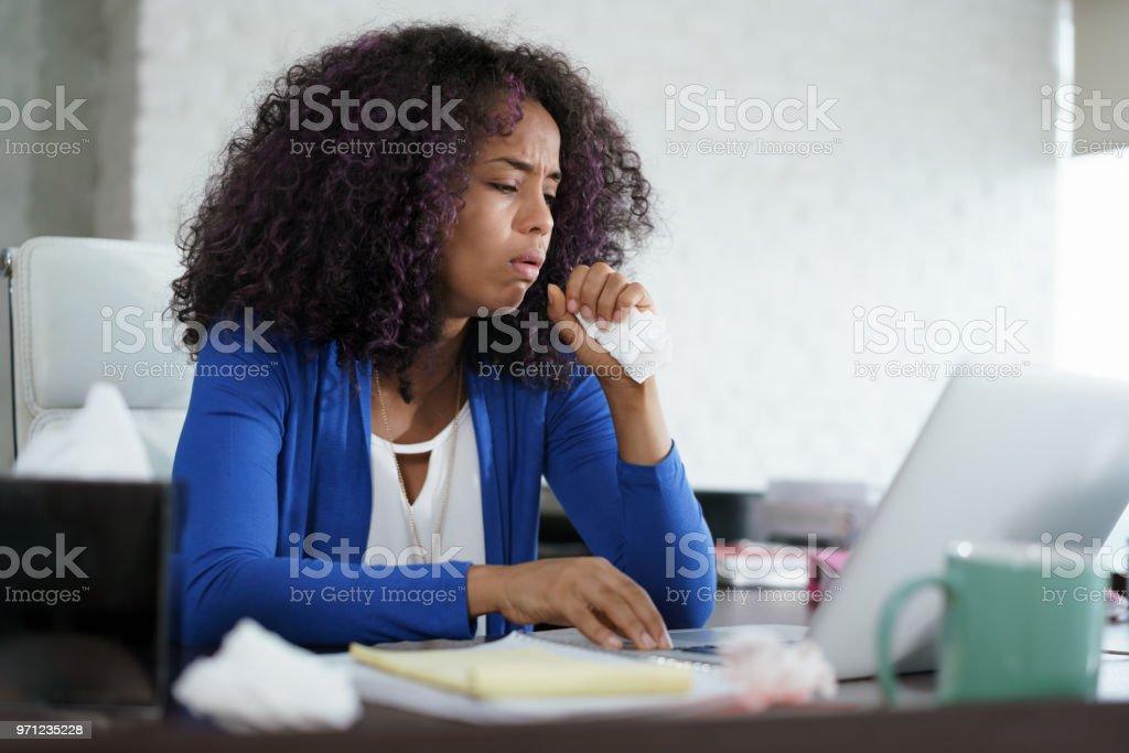 Mujer afroamericana que trabaja en casa tos y los estornudos - foto de stock
