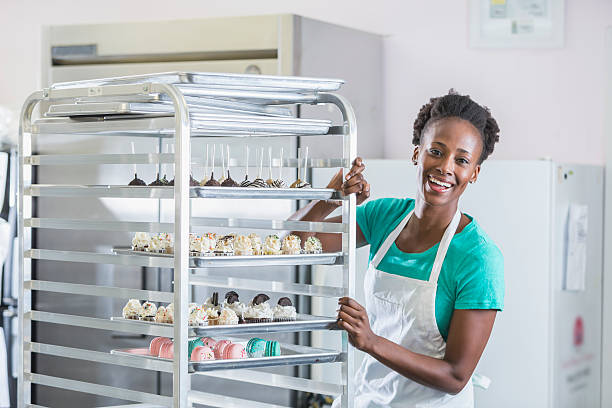african american woman working in bakery kitchen - süßigkeiten halter stock-fotos und bilder