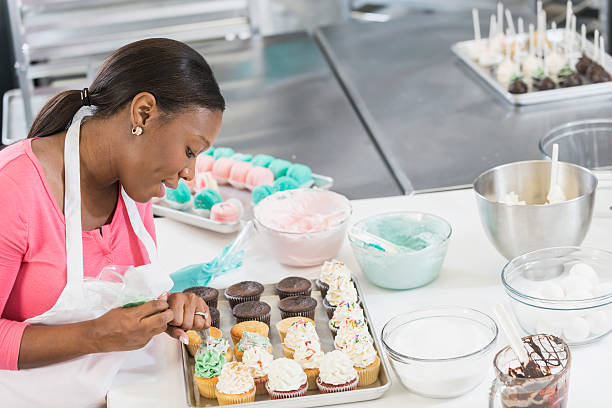African American woman working in bakery kitchen - foto stock