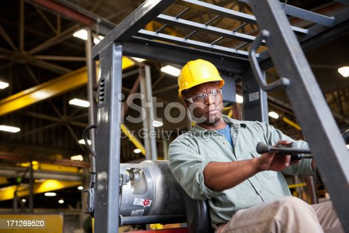 African American worker (30s) driving forklift in factory.