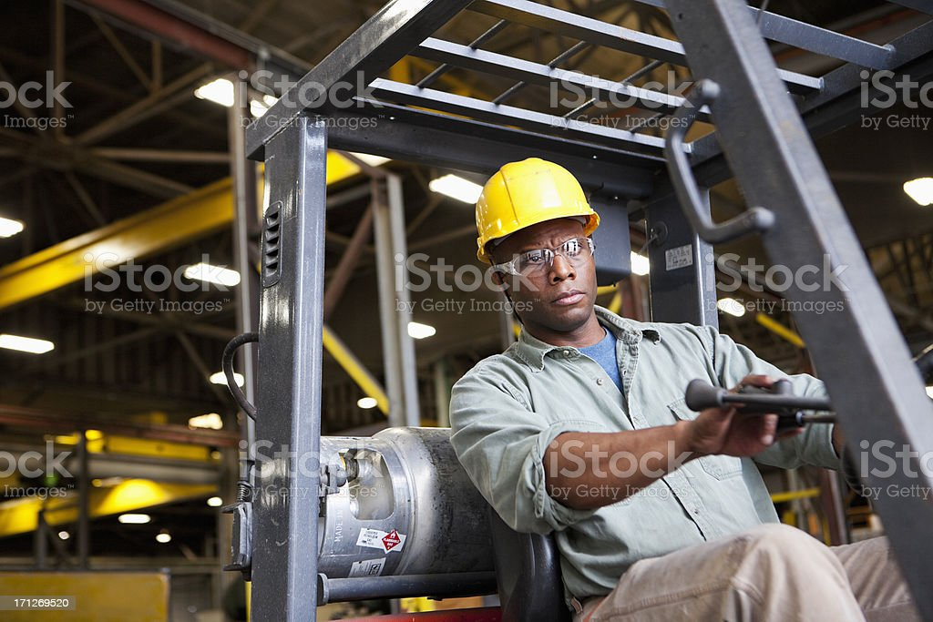 African American worker driving forklift stock photo
