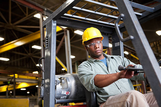 African American worker driving forklift African American worker (30s) driving forklift in factory. driver occupation stock pictures, royalty-free photos & images