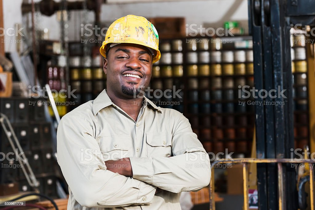 African American worker in print shop, next to forklift stock photo