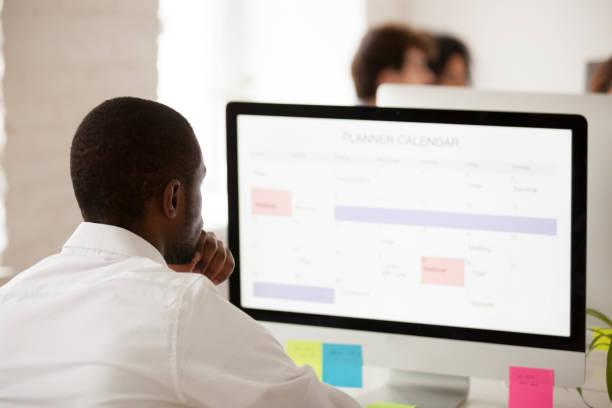 afrikanische amerikanische arbeiter planung arbeitsplan mit desktop-planer-kalender - leiterdisplay stock-fotos und bilder