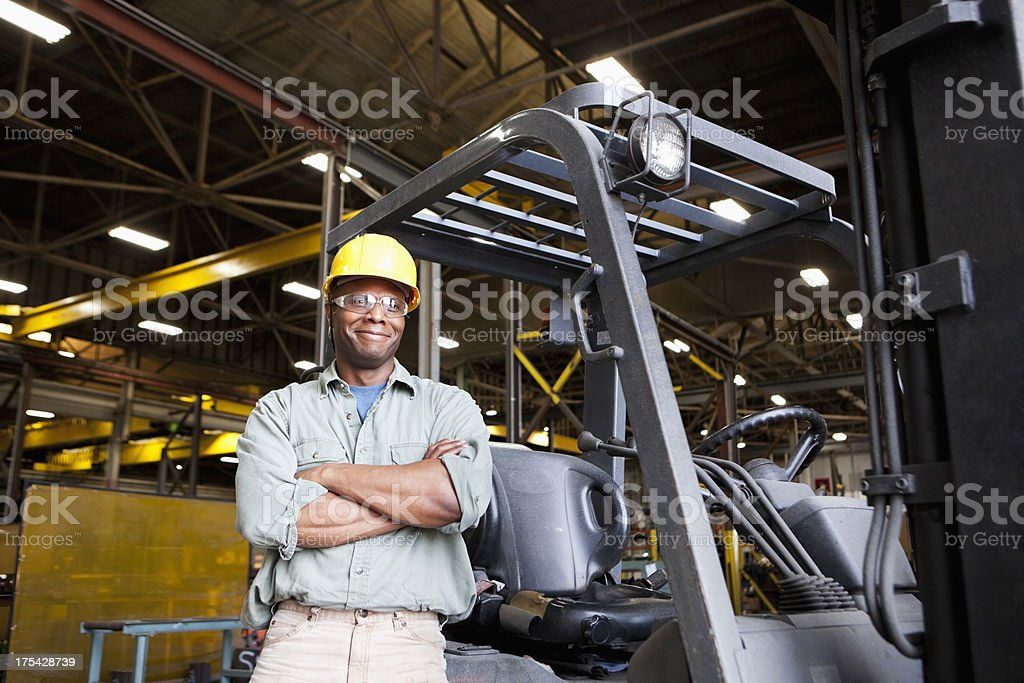 African American worker standing beside forklift stock photo