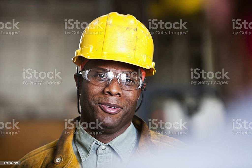 African American worker talking to co-worker stock photo