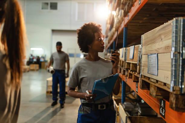 afro-amerikaanse werknemer met walkie-talkie tijdens het controleren van de voorraad in een magazijn. - warehouse worker stockfoto's en -beelden
