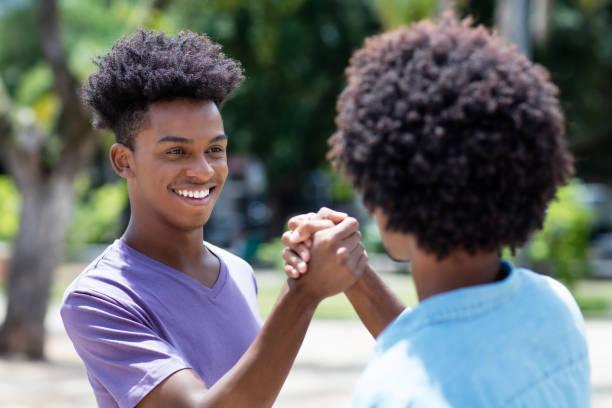 Afro americano joven adulto da alto cinco a amigo con pelo afro - foto de stock