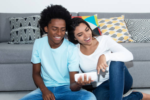 African american young adult watching movie with latin girlfriend stock photo