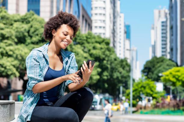 Afroamericana joven adulta mujer enviando sms mensaje con teléfono - foto de stock