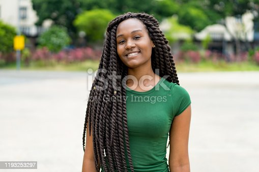 African american young adult woman with amazing hairstyle outdoor in summer in city