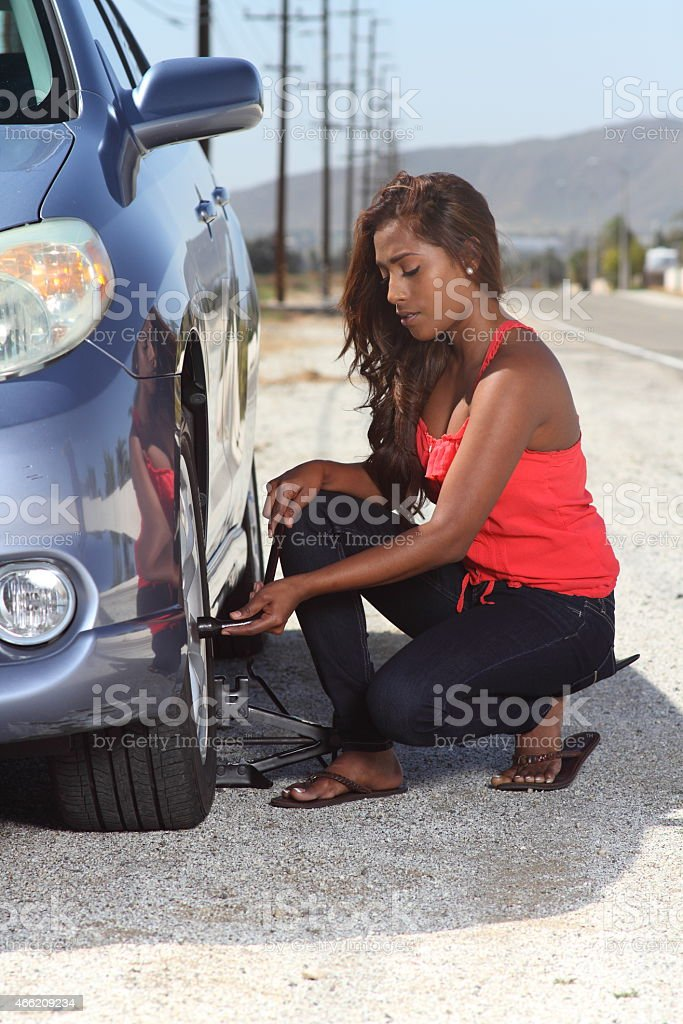 African American Young Driver Changes Car Tire Eyes Down Vertical stock photo