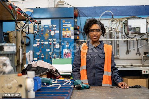 African american young female blue collar worker at a manufacturing factory standing behind work station smiling at camera - Industrial concepts