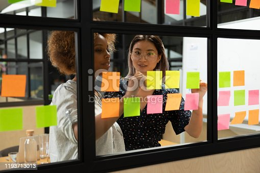 1147760705 istock photo African american young female scrum master working with vietnamese colleague. 1193713013