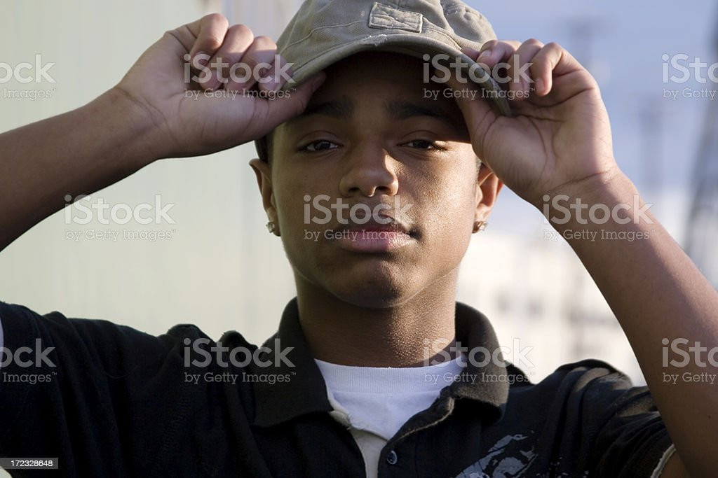 African American Young Man Putting on Baseball Cap Outside, Portrait royalty-free stock photo