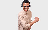 istock African American young man with headphones listen the music and dancing. Happy smiling Afro male wearing mirror sunglasses and casual outfit, posing over white studio background. People concept 1134194237