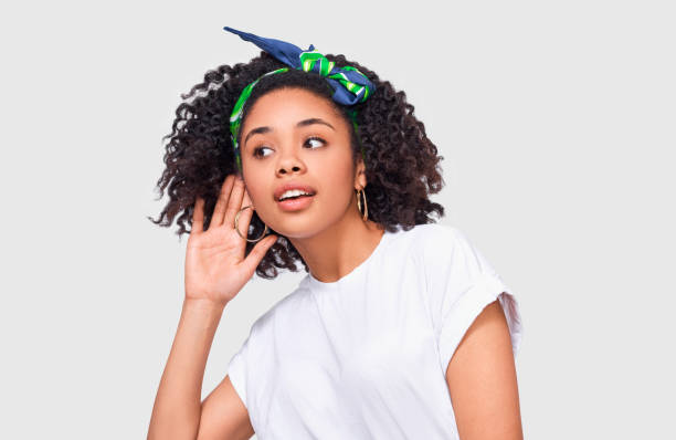 African American young woman paying attention and placing hand on ear asking someone to speak louder or whisper, isolated on white wall. Pretty Afro girl which overhears secret conversation stock photo