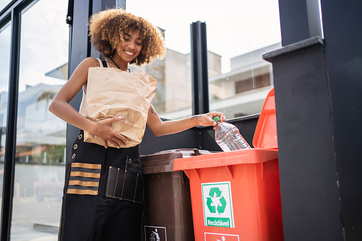 Young woman recycling garbage at home