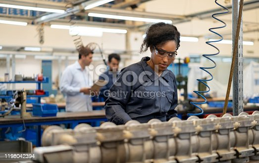 African american young woman working at an assembly production of water pumps at a factory - Incidental people at background