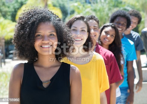 istock African and american and caucasian and hispanic young adults in a row 674755950