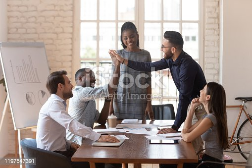 937843262 istock photo African and arab colleagues giving high five during group meeting 1197547391