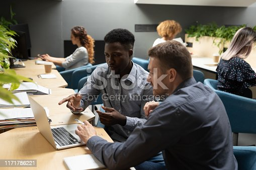 1085713886 istock photo African and caucasian colleagues discuss project using laptop in office 1171786221