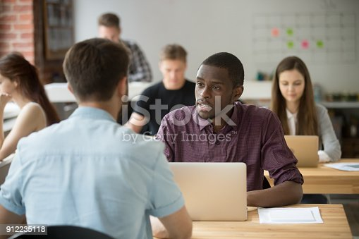 istock African and caucasian entrepreneurs discussing project in co-working office space 912235118