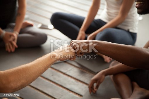 istock African and caucasian men fist bumping at group meeting, closeup 922482726