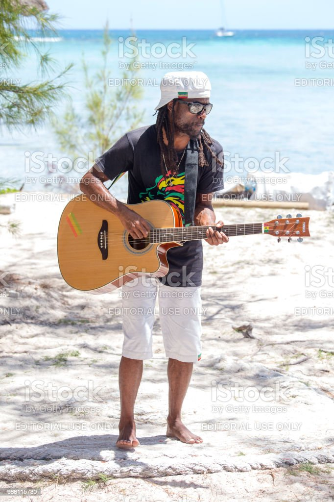 African animator plays guitar and dances for tourists. Island Mauritius stock photo