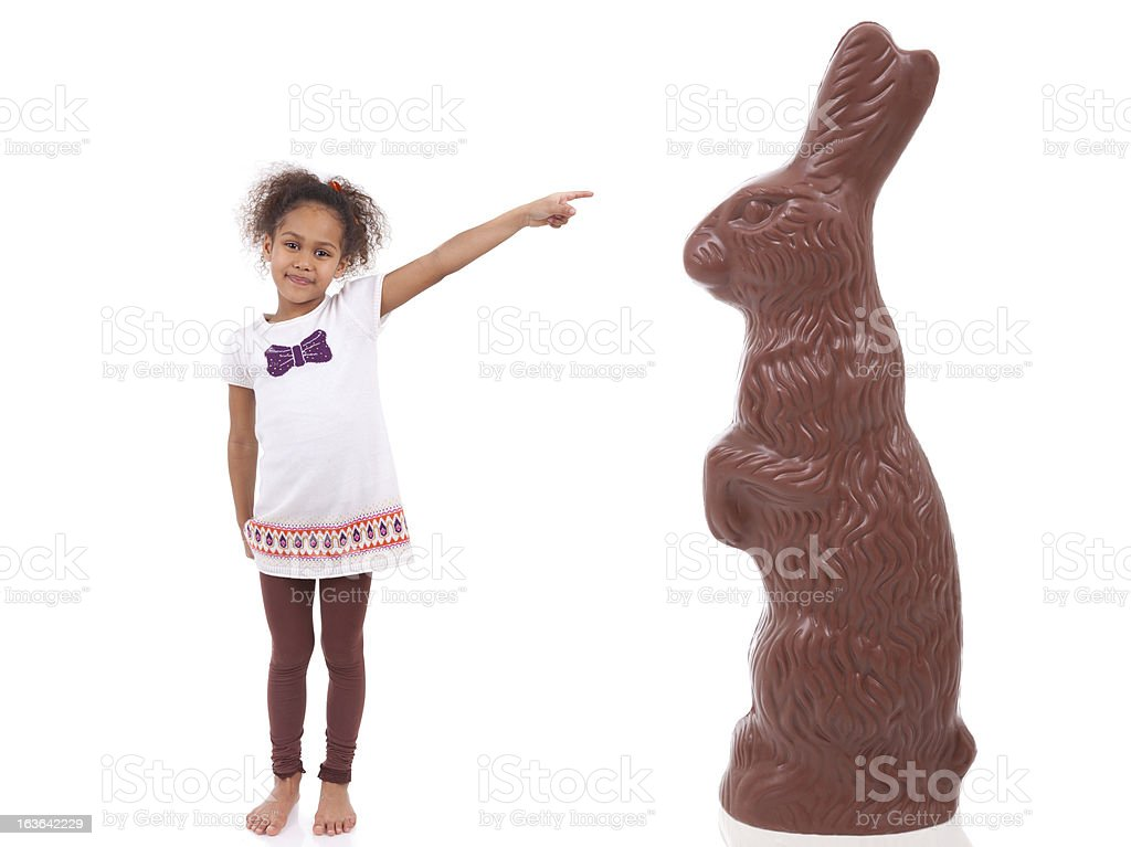African Asian girl pointing a giant chocolate rabbit royalty-free stock photo