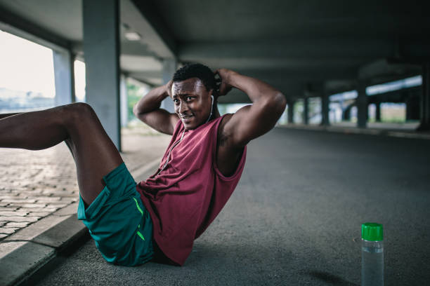 african athlete doing sit-ups outdoors - man city exercise abs foto e immagini stock