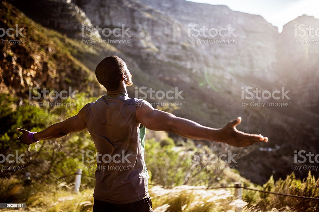 African athlete holding his arms out in the morning sun stock photo