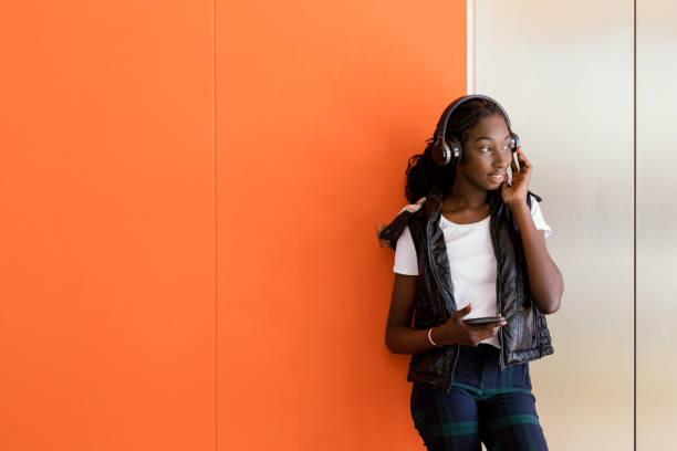 Afrikansk australisk tonårs flicka som lyssnar på musik under hörlurar bildbanksfoto